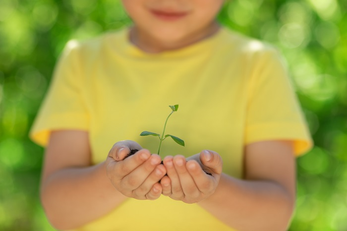 an eco-friendly child holding a plant